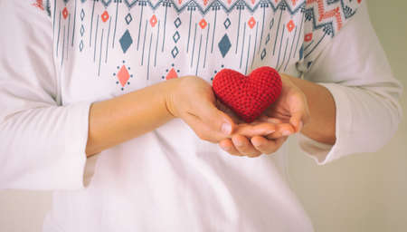 Women wear white shirt hand holding red heart. Concept of love, hope, happy valentine, healthcare,organ donation,insurance, medical, World heart day, National Organ Donor day,World mental health day.