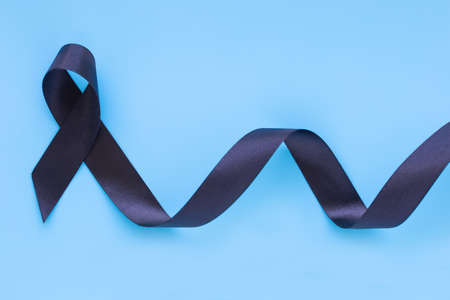 Black ribbon curl on blue isolated background with copy space, symbol of Skin Cancer awareness month on May, Melanoma cancer, Mourning ribbon symbolic. Healthcare medical and insurance concept.