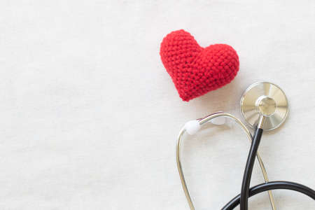 Red heart and stethoscope on white isolated background, copy space. Concept for heart health, cardiology, insurance plan, organ donation, doctor day, world heart day, pulse and hypertension disease.