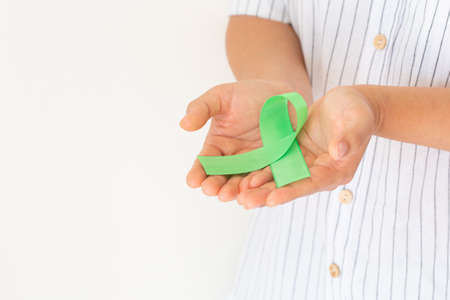 Hands holding emerald green or jade green ribbon on white background with copy space, symbol for Liver Cancer awareness, World Cancer Day. Healthcare or hospital and insurance concept.