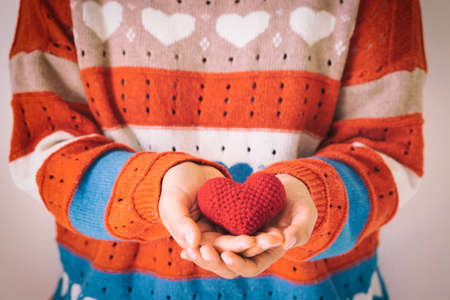 Women wear knit shirt hand holding red heart. Concept of love, hope, happy valentine, healthcare,organ donation,insurance, medical, World heart day, National Organ Donor day,World mental health day. Imagens