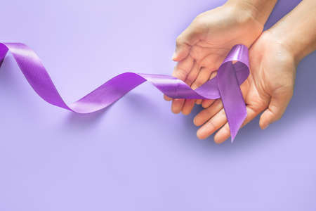 Hands holding purple or violet ribbon on purple background with copy space. Pancreatic Cancer Testicular Cancer Awareness Cancer Survivor Leiomyosarcoma World Cancer Day. Healthcare, insurance concept