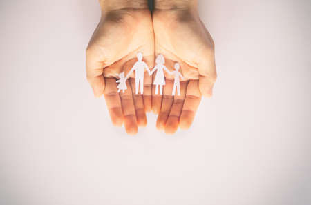 Hand holding family paper cut on white background. Family day concept, foster care, domestic violence, homeschool, international day of families, world mental health day, world autism awareness day