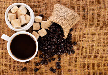 Coffee cup and coffee beans on sack