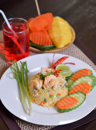Fried rice with shrimp on a white dish on wooden table