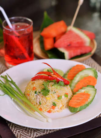 Fried rice with shrimp on the white dish on wooden table Standard-Bild - 163359750