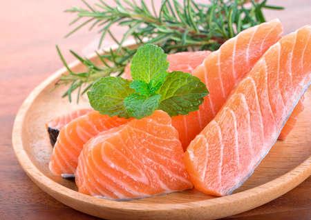 Fresh raw salmon fillet on wooden plate. Standard-Bild - 163360174