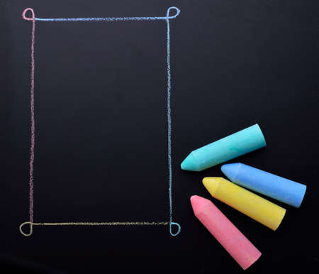 Colored chalk on a dark school board. The concept of children's creativity games, back to school. Blackboard with multicolored strokes from the chalk. Background texture with place for text, flat lay. Standard-Bild
