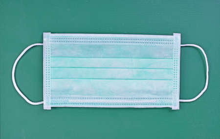 Disposable face mask isolated on green background Standard-Bild