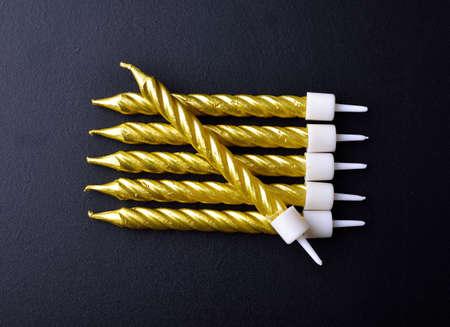 Golden Birthday candles on black background Standard-Bild