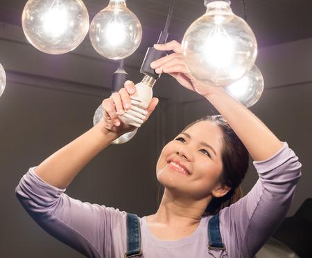 femme asiatique changer ampoule Banque d'images