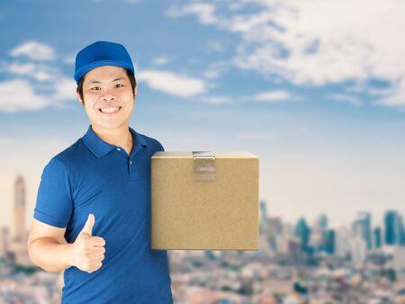 warehouseman: asian delivery man holding carton box with thumb up