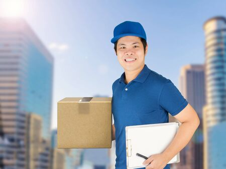 consign: asian delivery man holding carton box and notepad