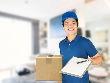 warehouseman: asian delivery man holding carton box and notepad