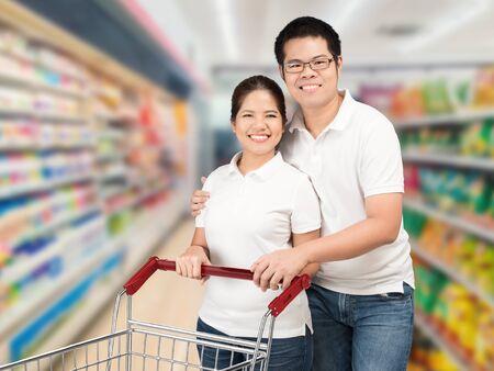 pushcart: asian couple shopping in supermarket