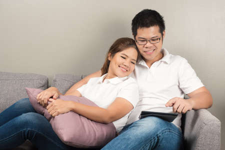 couch: asian couple relaxing on couch
