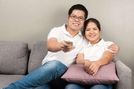 pareja viendo television: Pares asiáticos viendo la televisión en casa