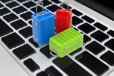 online booking concept with 3d rendering travel luggage on keyboard Stock Photo