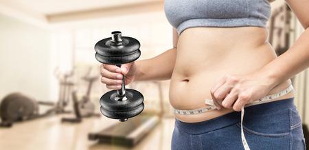 levantar peso: mujer con sobrepeso mano que sostiene la cinta métrica y pesa de gimnasia