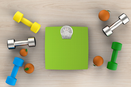 weight loss success: healthcare concept with weight scales with dumbbells and oranges