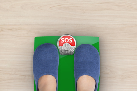 kilograms: foot standing on weight scales with text sos