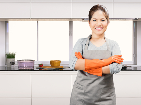 rubber gloves: asian housewife wearing rubber gloves in kitchen