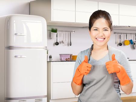 asiático ama de casa con guantes de goma pulgares para arriba