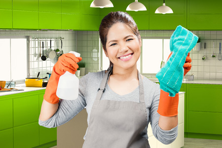 ama de llaves: asian housekeeper holding spray bottle and rag with kitchen background