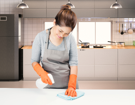 chores: asian housekeeper cleaning on table with kitchen background Stock Photo