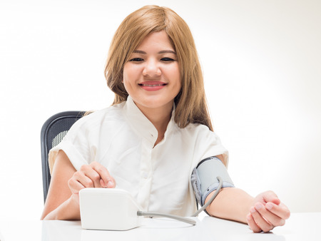 self testing: woman checking blood pressure on white background
