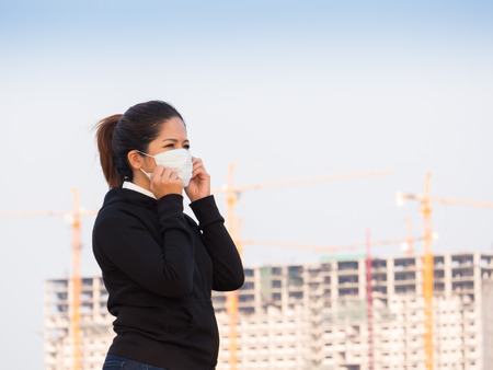 deterrence: asian woman wearing face mask with construction background