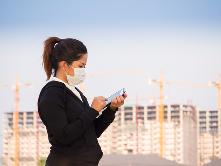 deterrence: asian woman wearing face mask and working with construction background