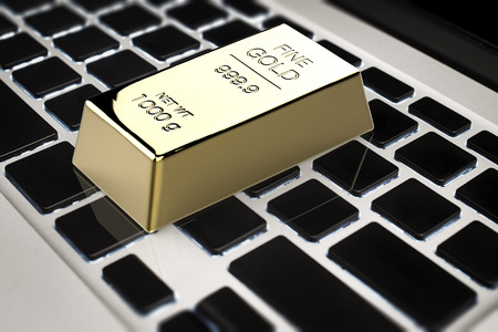gold bar: online gold trade concept with 3d rendering gold bar on keyboard