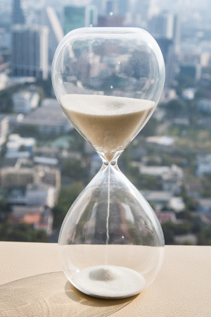 hourglass or sandglass with cityscape background