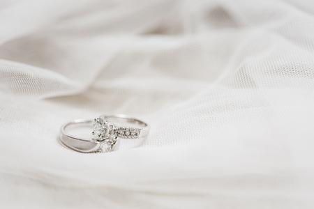 tela blanca: dos anillos de boda en una tela blanca Foto de archivo