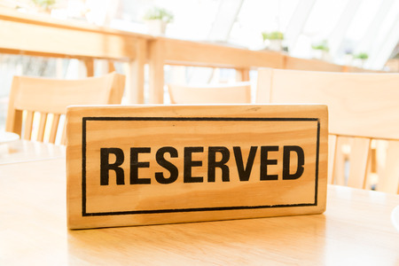 reserved sign: wooden reserved sign on table Stock Photo