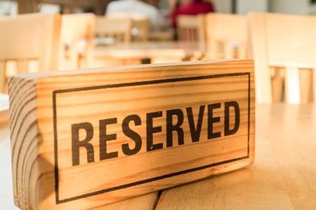 booked: wooden reserved sign on table Stock Photo