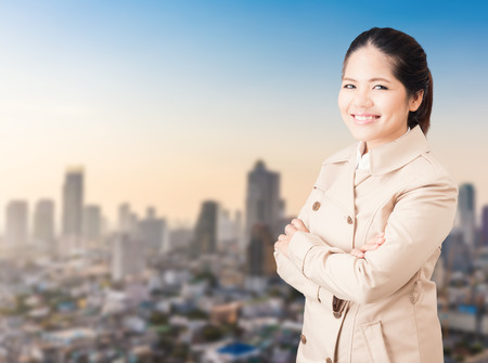 asian businesswoman arm crossed and wearing brown coat Stock Photo