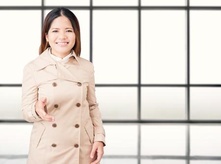 extending: asian woman wearing brown coat extending hand to shake