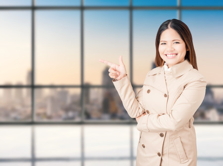 asian businesswoman pointing finger with cityscape background Stock Photo