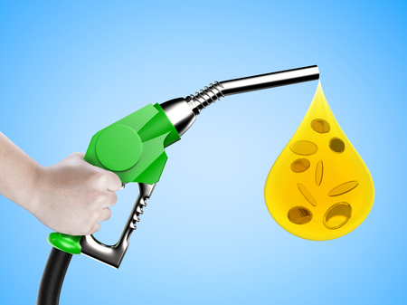 hand holding gas pump nozzle with oil drop and gold coins on blue background