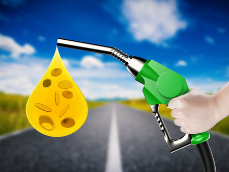 gas nozzle: hand holding gas pump nozzle with oil drop and gold coins Stock Photo