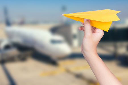 hand holding paper: happy flight concept with hand holding paper plane with airplane blurred background