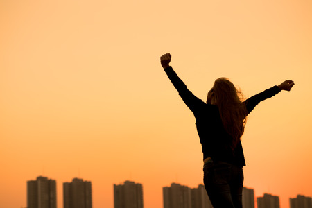 fresh concept: silhouette success woman hands up with sunset sky background