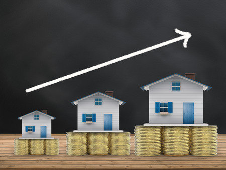 house exchange: real estate investment concept with mock up houses and gold coins