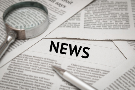newsfeed: news headline on newspaper background Stock Photo