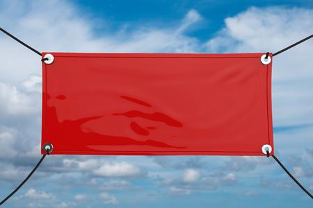 ロープでぶら下がっている赤い空のビニール バナー 写真素材