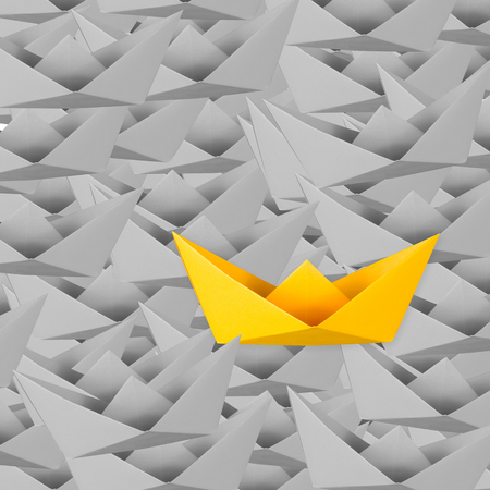 differentiation: differentiation concept with yellow paper boat among grey paper boats Stock Photo