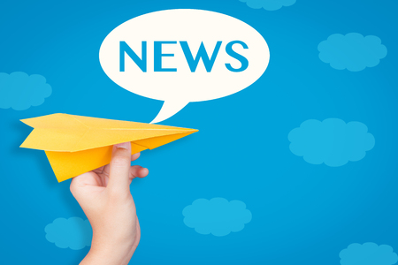 hand holding paper: hand holding paper plane with news text in speech bubble on blue background