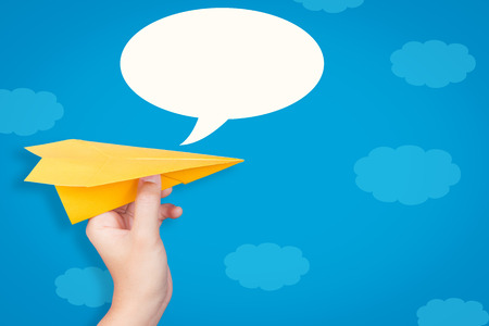 hand holding paper: hand holding paper plane with speech bubble on blue background